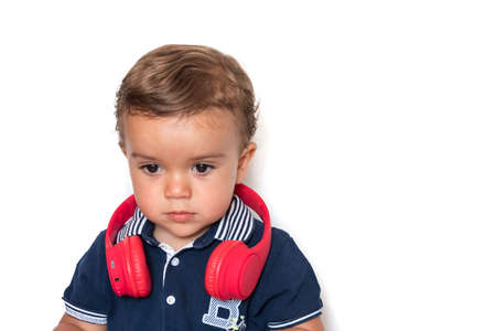child watching videos on mobile phone with red headphones and dark blue shirt Stockfoto - 155219747