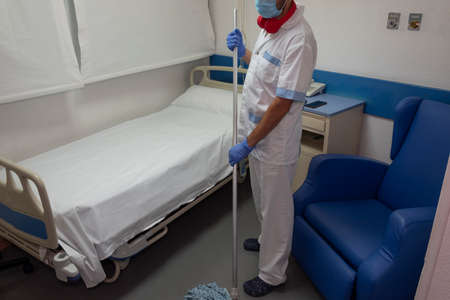Male cleaning staff perform cleaning and disinfection tasks in the hospital.