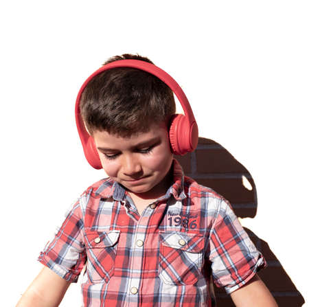 Portrait of a child listening to music with headphones on a white brick background Stockfoto - 154962255