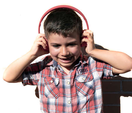 Portrait of a child listening to music with headphones on a white brick background