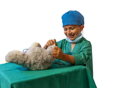 concept of a child's vocation playing doctor-surgeon operating a teddy bear.