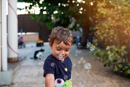 child with blue t-shirt playing with soap bubbles