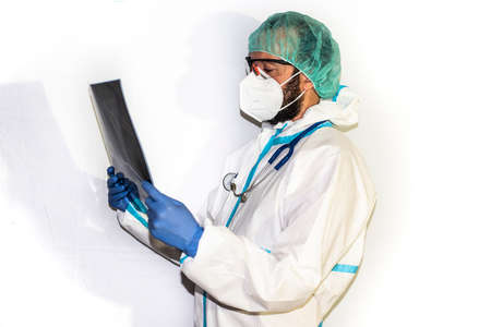 Middle-aged male doctor dressed in protective gear and stethoscope standing on an isolated white background facing the camera. Concerned person.