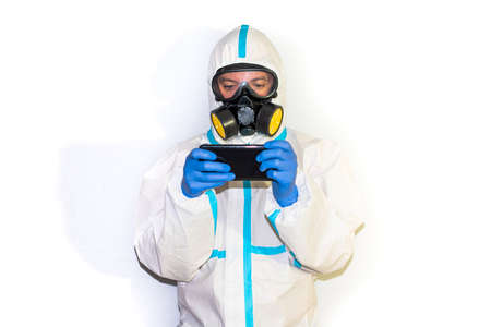 doctor in safety suit on white background. protection against coronavirus. mobile phone.