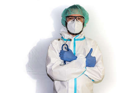 Middle-aged male doctor dressed in protective gear and stethoscope standing on an isolated white background facing the camera. Positive person.