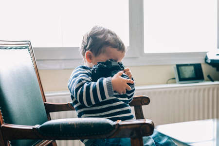 Curious child explores camera sitting on a chair
