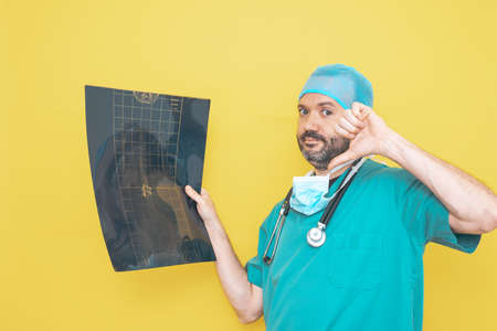 Trauma surgeon dressed in operating theater uniform and stethoscope, reviewing X-ray with a concerned gesture, all against a yellow background.