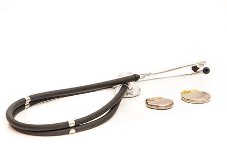 TWO PACEMAKER BATTERIES SURROUNDED BY A STETHOSCOPE WHITE BACKGROUND Stockfoto