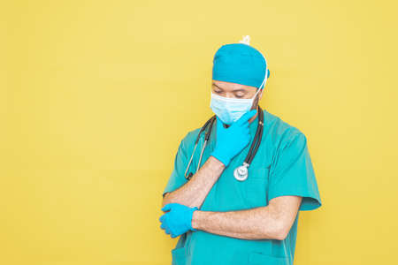 doctor dressed as a surgeon in green with stethoscope and mask on a yellow background with a worried expression.