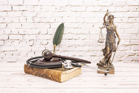 stethoscope with judge's gavel and symbol of justice. Concept of medical injuries.