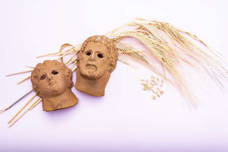 representation of a Roman god's head on a bouquet of dried wheat on a pink background