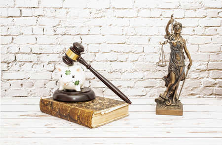 Piggy bank on judge's gavel next to symbol of justice. Savings concept with security.