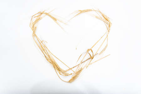 heart-shaped dried wheat on a pink background