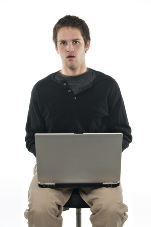teenage boy on white background with laptop looking confused photo