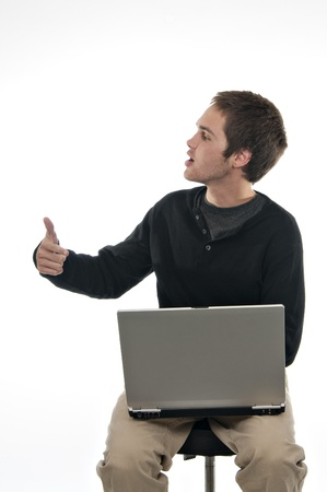 teenage boy with laptop computer giving thumbs up photo