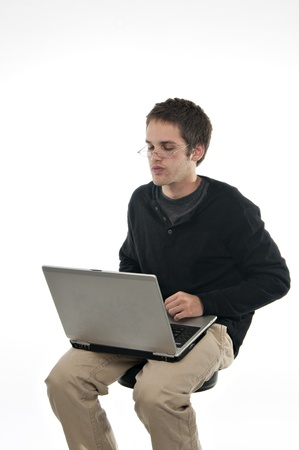 teenager sitting on stool looking through glasses at laptop on white background photo