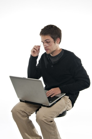 teenage boy looking over glasses at laptop computer photo