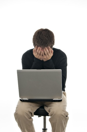 teenager sitting on stool with laptop and his hands covering his face on white background photo