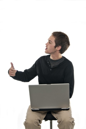 teenager sitting on stool with laptop bringing attention to laptop on white background photo