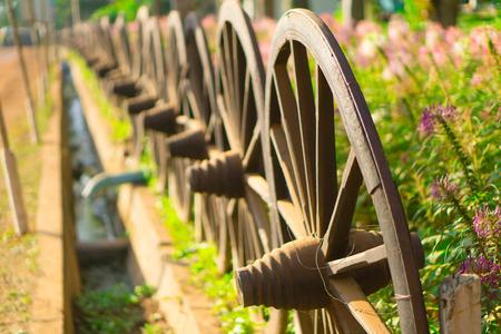 Old wooden wheel on hay, flower garden Stock Photo