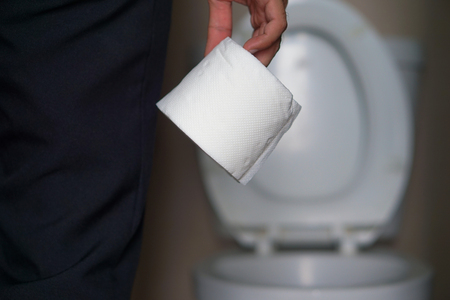 The young man holds a toilet paper roll.
