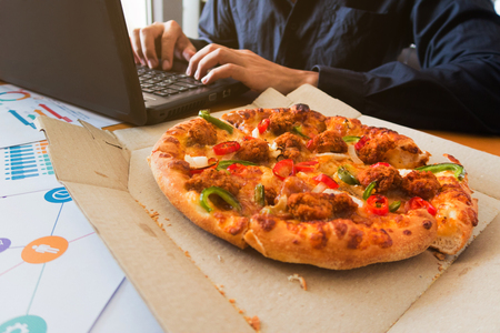 Young man eating pizza during work.