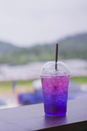 Purple water in a plastic cup, the background is a coffee shop.