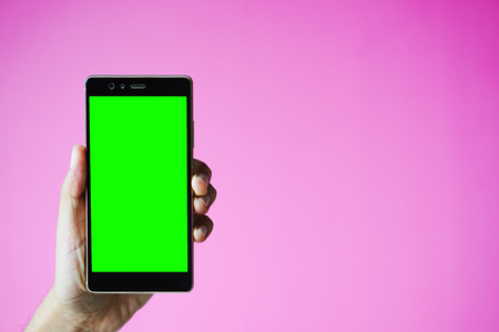 Cell phone in hand Pink background.