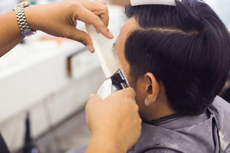 Male customer is cutting hair by hairdresser.