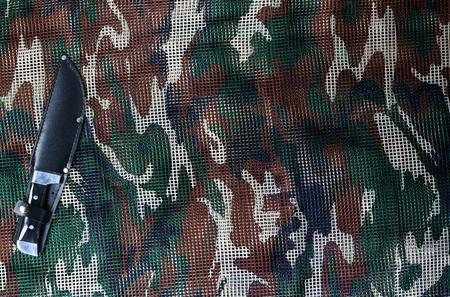 Knife on military camouflage net background Stock Photo