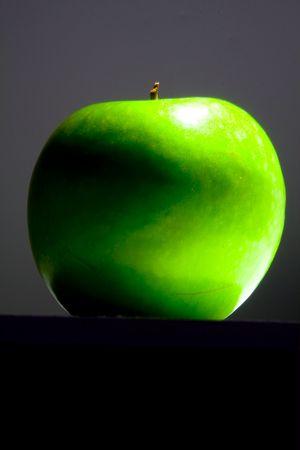 Lush, shiny, crisp, green Granny smith apple. Highlighted by single spotlight against a dark background. photo