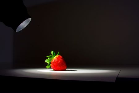 Lucious, ripe, red , juicy strawberry highlighted by a single spotlight against a dark background.