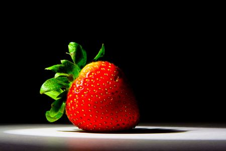 Lucious, ripe, red , juicy strawberry highlighted by a single spotlight against a dark background. photo