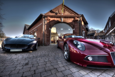 HDR Image of 2 Sports cars outside a brick building on a cobbled street photo