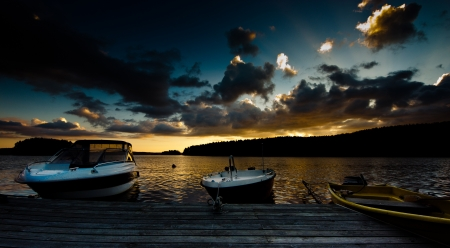 3 Small powerboats moored on a jetty with a sunset on the background photo