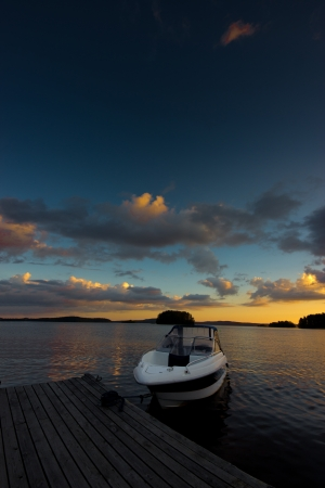 A power boat moored against a sunset on a calm lake photo