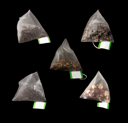 5Luxury teabags isolated on black with label in Pyramid teabag photo
