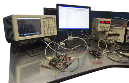 Isolated electronic engineer work bench with connected circuitboard for testing photo