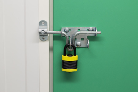 self storage: Close up image of a Black and Yellow on a self storage unit with a green door