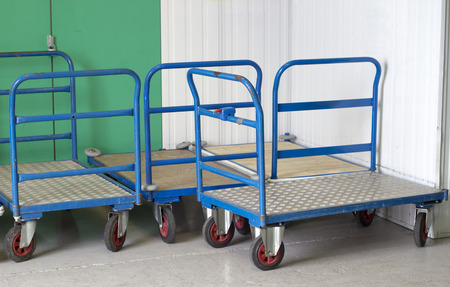 self storage: Trolleys at self storage centre with blue handles Stock Photo