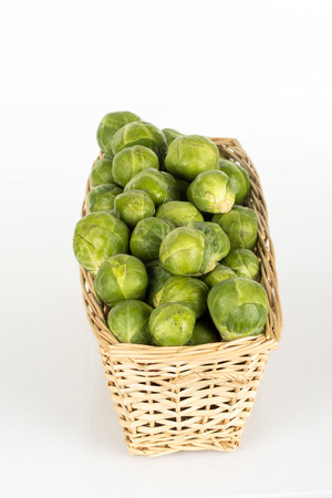 Straw basked full of brussels sprouts isolated on white background photo