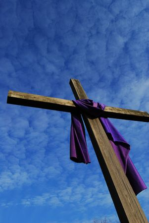 Old wooden cross against the sky with a scard of purple fabric hanging from it photo