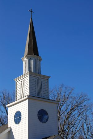 A White country church steeple against a beautiful blue winter sky.
