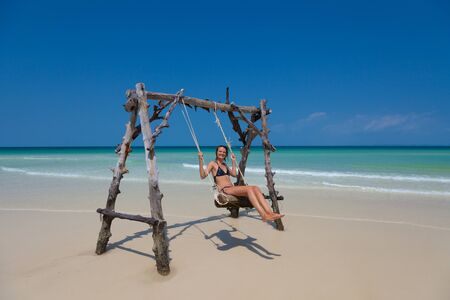 Young cheerful woman relaxing on a swing at the turquoise ocean on a paradise beach and vacationing in a tropical country