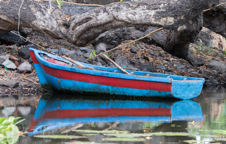 Old colorful row boat tied up to the shore on Lake Nicaragua, Granada, Nicaragua, 3 Mar 2016