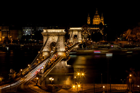 Chain Bridge crossing the Danube with St. Stephens Basilica in the background illuminated at night, Budapest, Hungary