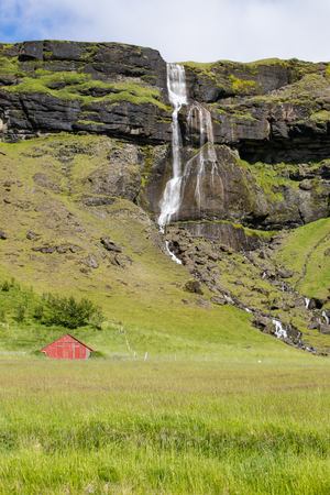 Waterfall and stream along the South Coast of Iceland with a red barn Фото со стока