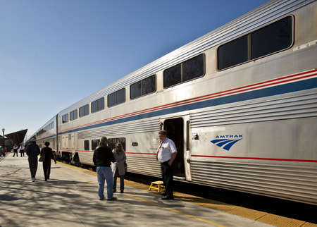 AmTrak Conductor and passengers on a sunny platform.