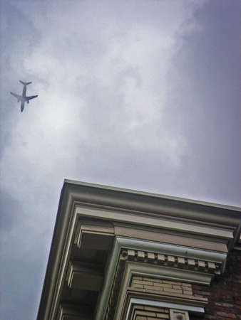 outbound: A Plane Flying Over a Building Corner.