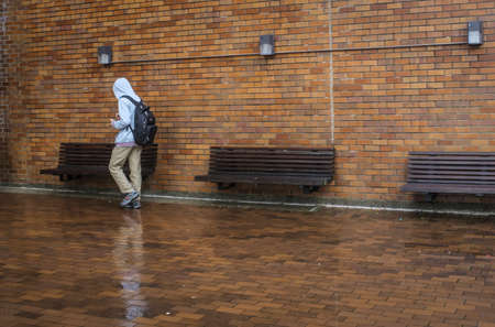 An alone figure in a hoodie in the rain at the University of Washington. Stock Photo